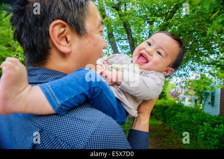 Metà adulto padre giocando con il bambino figlio in giardino Foto Stock