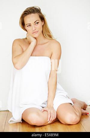 Donna incinta seduta sul pavimento con asciugamano Foto Stock
