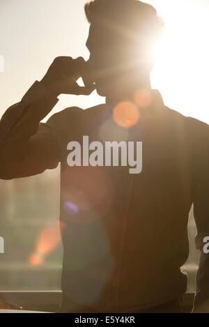 L'uomo parlando al cellulare, stagliano dal sole che splende attraverso la finestra Foto Stock
