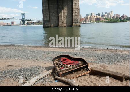 Un pianoforte abbandonati sulla formata naturalmente spiaggia sotto il ponte di Brooklyn sull'East River a Manhattan. Foto Stock