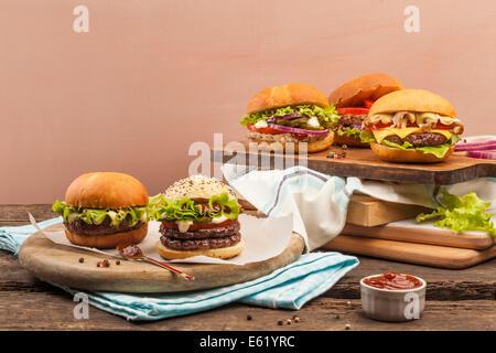 Cinque diversi tipi di hamburger gourmet su sfondo di legno Foto Stock