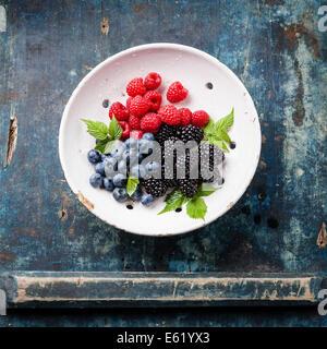 Mix di frutti di bosco freschi con foglie d'annata scolapasta in ceramica blu su sfondo di legno Foto Stock