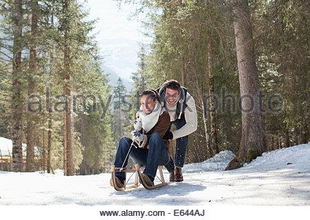 Coppia sorridente slittino in boschi innevati Foto Stock
