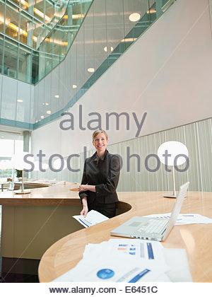 Imprenditrice in piedi in ufficio Foto Stock