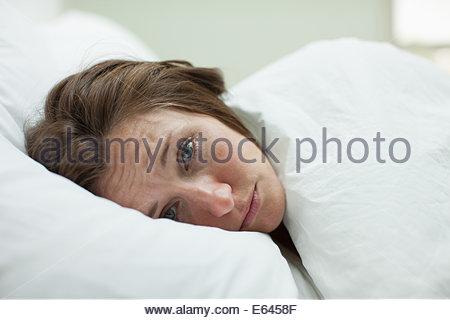 Malata che stabilisce nel letto sotto coperta Foto Stock