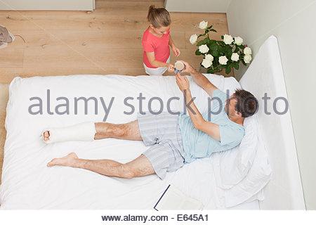 Figlia di portare il caffè al Padre con la gamba rotta Foto Stock