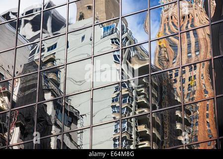 Riflessi distorti di edifici ad alta in una parete di vetro di un altro grattacielo a Manhattan. New York, Stati Uniti d'America.
