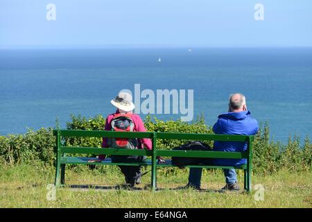 Un giovane che guarda al mare mentre si è seduti su una panchina a Jerbourg Point, Guernsey, Isole del Canale, GB Foto Stock