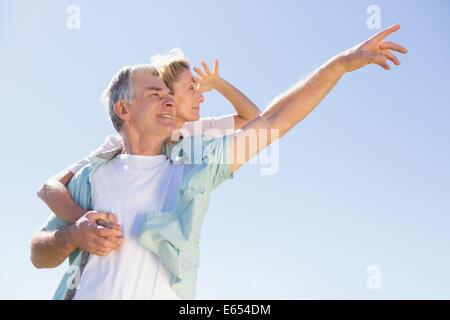 Felice l'uomo senior dando il suo partner un piggy back