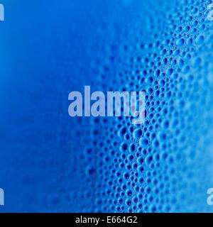 Gocce d'acqua in bottiglia blu sullo sfondo Foto Stock