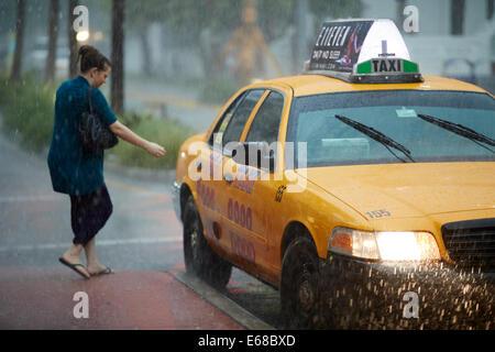 Una donna bandiere verso il basso un taxi giallo di uscire dalla pioggia in Miami Florida Foto Stock