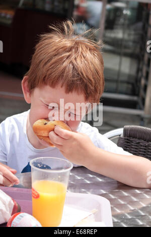 Un bambino di cinque anni, ragazzo di mangiare una ciambella a La Brioche Doree, Francia