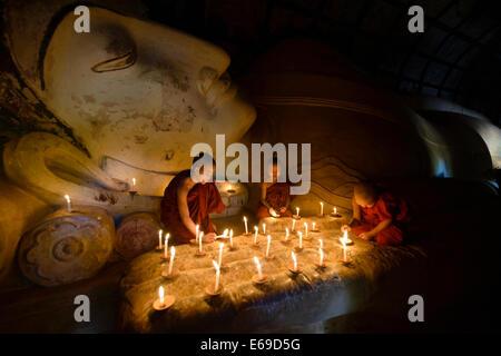 Monaci asiatici accendendo candele nel tempio Foto Stock