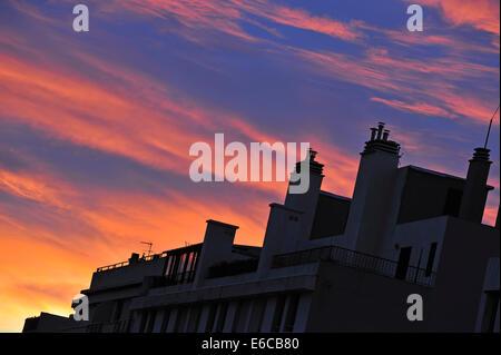 Costruzione di silhouette a sunrise / tramonto con cielo rosso Foto Stock