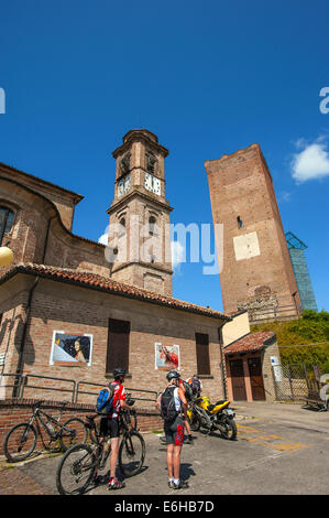 Italia Piemonte Langa del Barbaresco ciclisti e la chiesa parrocchiale di San Giovanni Battista Foto Stock