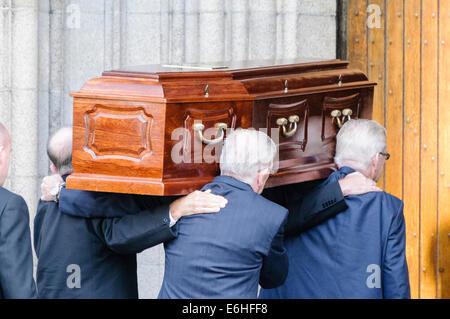 Quattro uomini trasportano una bara in una chiesa come parte di un servizio funebre.