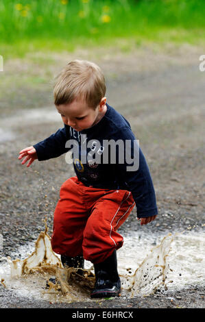 Un giovane ragazzo getting imbevuto in esecuzione su una pozzanghera Foto Stock