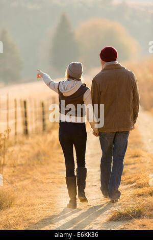 Vista posteriore della coppia giovane a piedi nella strada di campagna Foto Stock