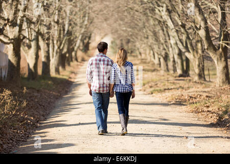 Vista posteriore del giovane tenendo le mani a piedi nella campagna di autunno Foto Stock