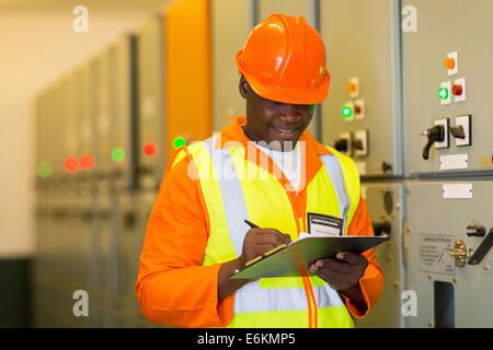 African ingegnere elettrico nella sottostazione sala di controllo Foto Stock