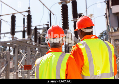 Vista posteriore di due ingegneri elettrici nella sottostazione Foto Stock