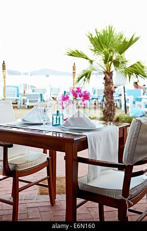 Esplorare la cucina turca con un affresco di al tavolo e sedie per il pasto sulla spiaggia di Bitez, Turchia Foto Stock