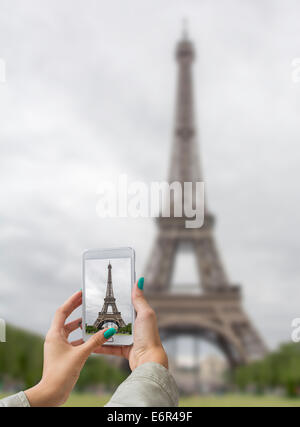 Giovane ragazza in viaggio e preso le immagini della Torre Eiffel, con telefono mobile Foto Stock
