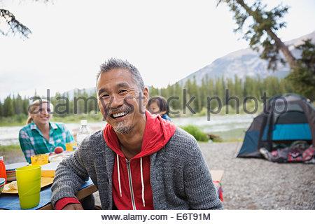 Uomo sorridente al tavolo da picnic al campeggio Foto Stock