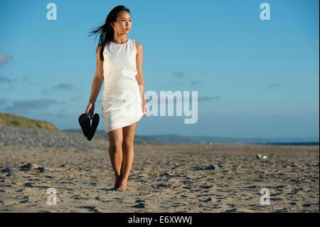 Un giovane di etnia cinese asiatica Ragazza donna che indossa un abito bianco tenendo le sue scarpe da solo a piedi lungo una spiaggia di sabbia fine estate REGNO UNITO