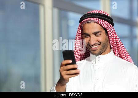 Arab arabia imprenditore lavora con il suo telefono cellulare con un edificio di uffici in background Foto Stock