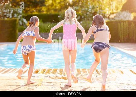 Un gruppo di ragazze salto in Piscina esterna Foto Stock