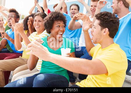 Gli spettatori nei colori della squadra la visione di eventi sportivi Foto Stock