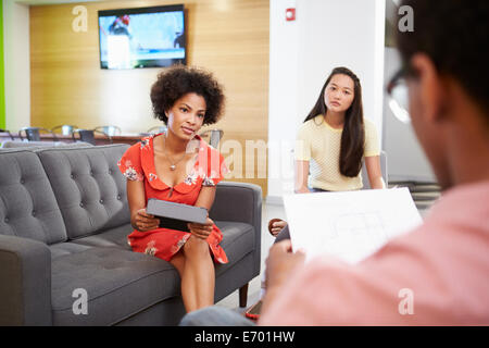 I Creative avente una riunione informale su divani in Design Studio Foto Stock