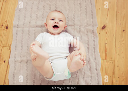 Ritratto di sorridere Bimbo giacente su una coperta Foto Stock