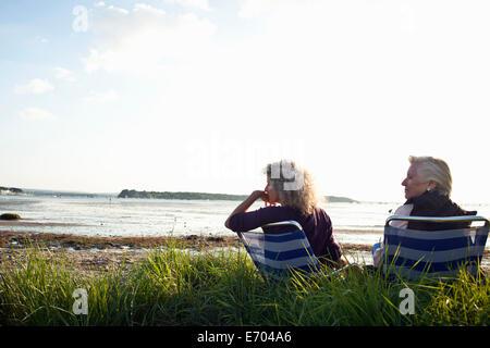 Madre e figlia gode di vista sulla spiaggia Foto Stock