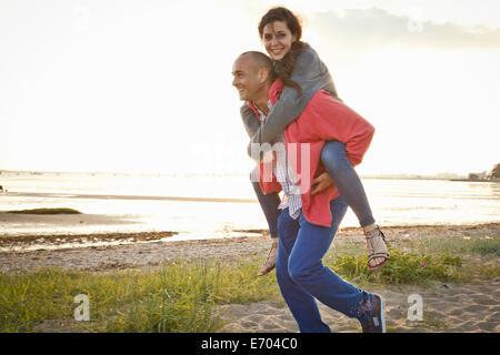 L uomo dando piggyback ride di donna sulla spiaggia Foto Stock