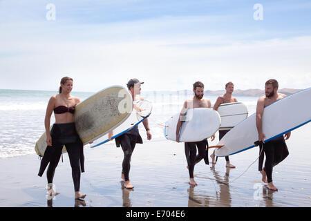 Gruppo di maschio e femmina surfer amici a piedi dal mare con tavole da surf