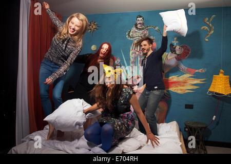 Quattro amici adulti aventi lotta di cuscini sul letto di hotel Foto Stock
