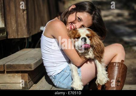 Ritratto di ragazza sorridente abbracciando il cane sui passi Foto Stock