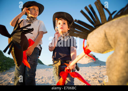 Due fratelli vestito da cowboy con la pistola giocattolo e hobby del cavallo Foto Stock