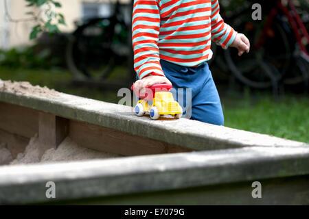 Ritagliato colpo di toddler maschio spingendo giocattolo auto intorno la sabbia in giardino Foto Stock