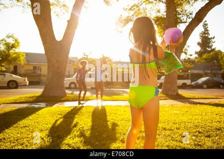 Ragazza a caccia di amici con acqua palloncino in giardino Foto Stock