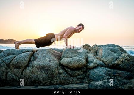 Metà uomo adulto facendo push-up su rocce in spiaggia Foto Stock