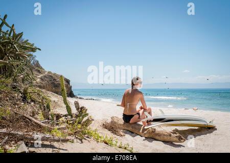 Giovane donna seduta su driftwood presso la spiaggia, le tavole da surf dal suo lato Foto Stock