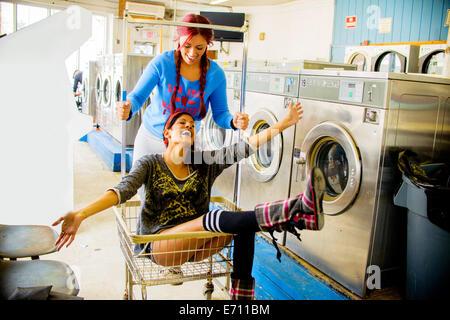 Due giovani donne in lavanderia a gettoni, uno spingendo il loro lungo nel carrello Foto Stock