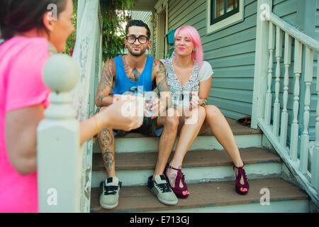 Giovani amici adulti chat sul portico passi Foto Stock