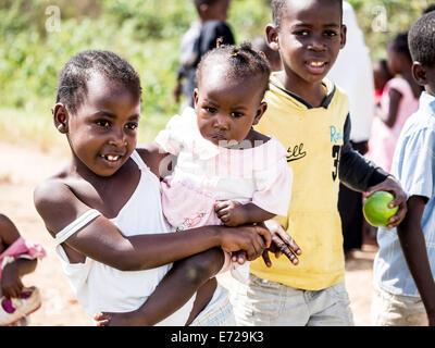 Bambini locali a chiedere alle persone di prendere le loro foto in uno dei villaggi sulla isola di Zanzibar, Tanzania Africa Orientale. Posizione orizzontale