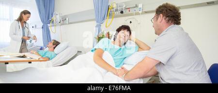 Uomo che parla alla moglie nella stanza di ospedale Foto Stock
