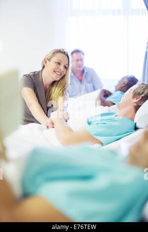 Donna che parla al ragazzo nella stanza di ospedale Foto Stock