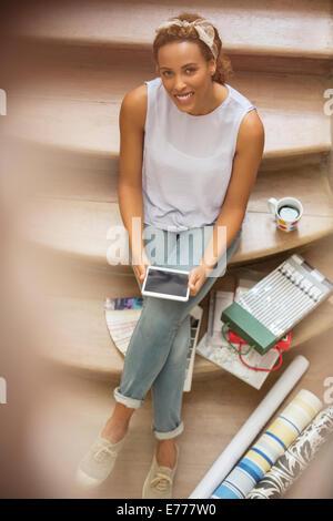 Donna con tavoletta digitale mentre è seduto sulle scale Foto Stock